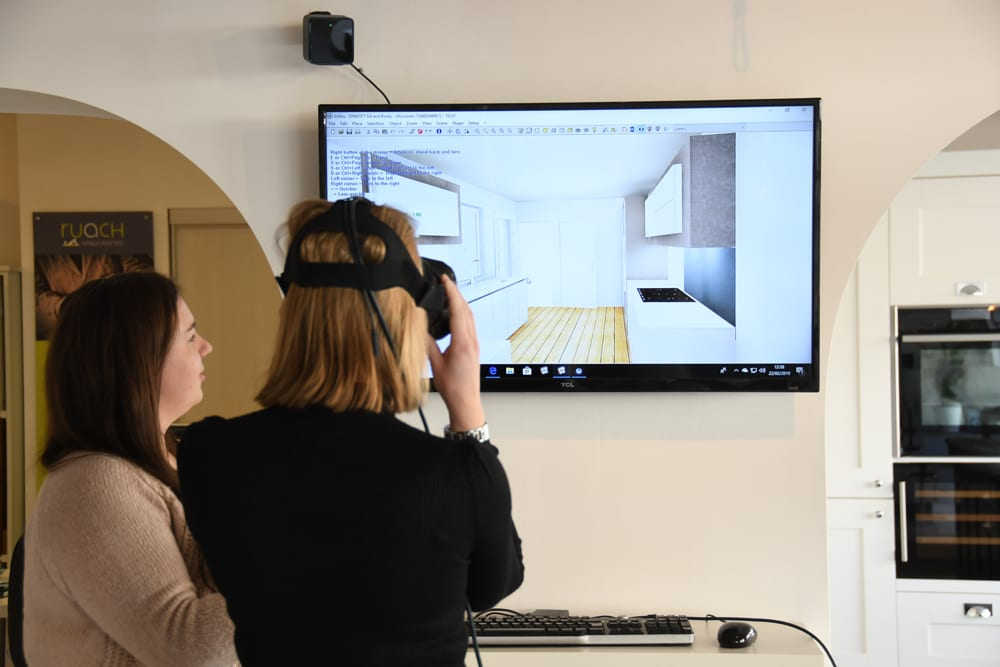 a customer tryin gout the virtual reality headset with her kitchen design whilst the designer stands next to her watching on the screen