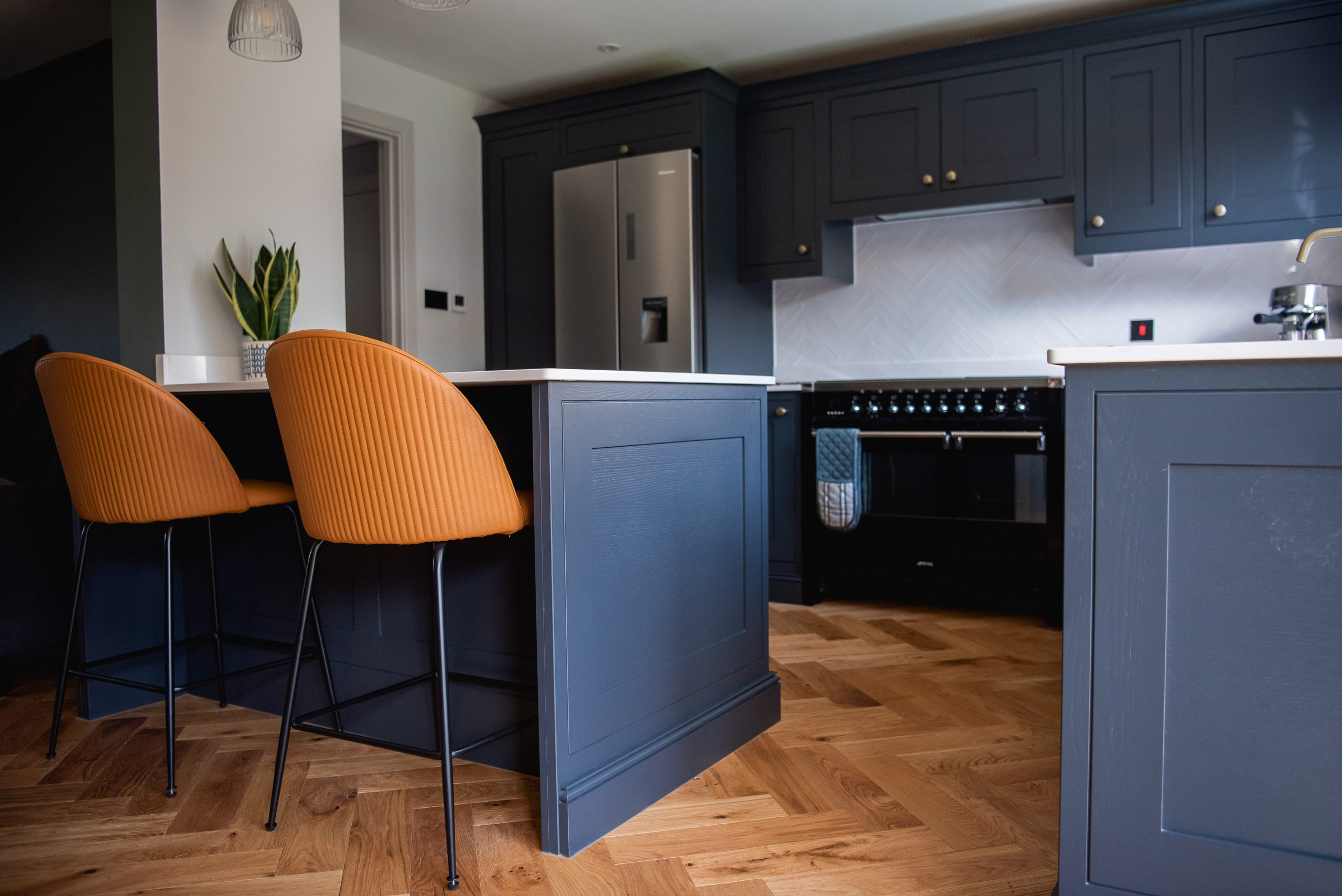 Black shaker kitchen with brass knobs and Silestone worktops with a breakfast bar