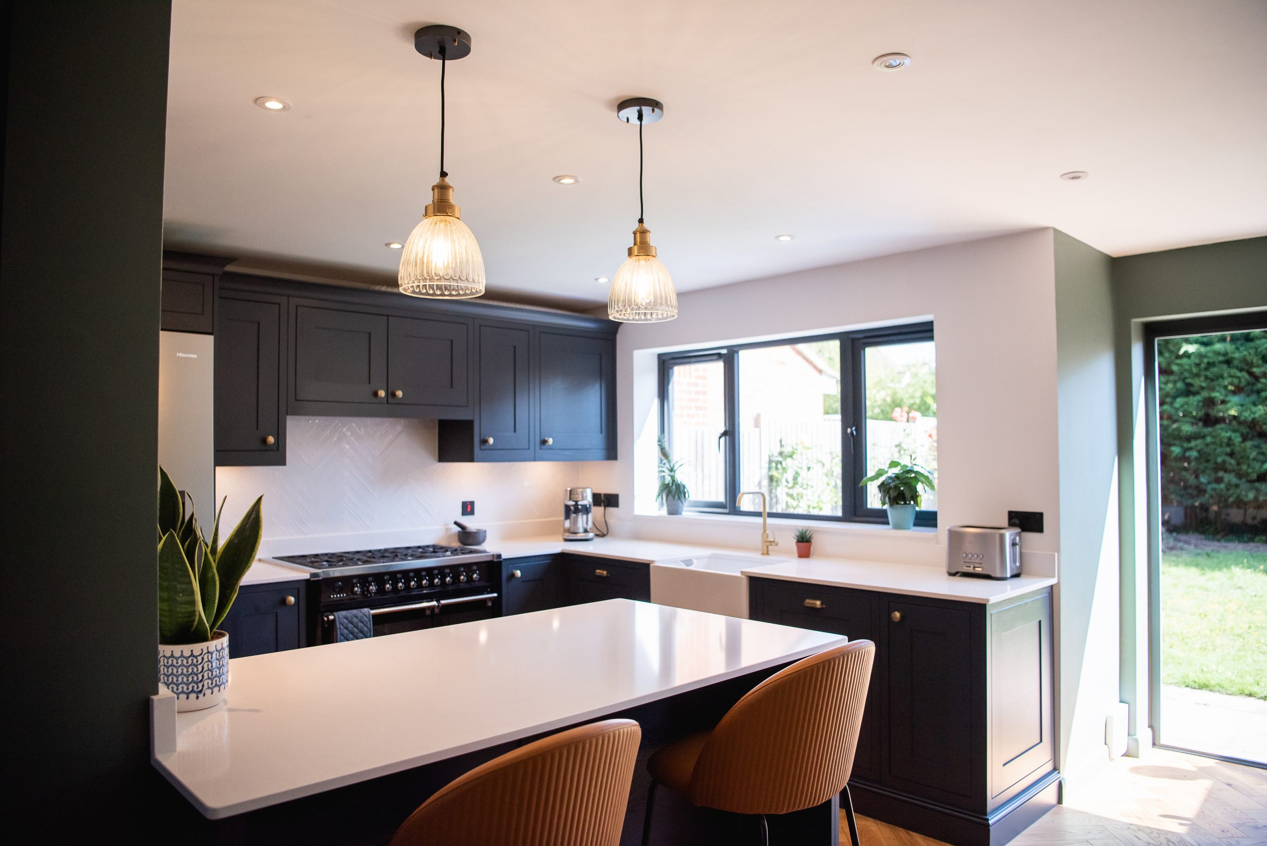 Black shaker kitchen with brass knobs and Silestone worktop and breakfast bar