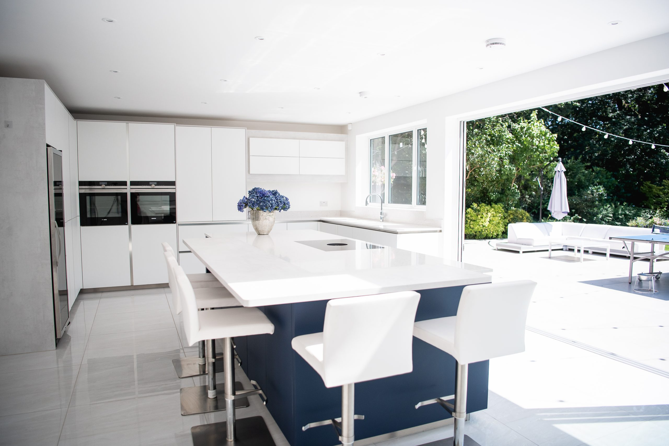White kitchen extension with blue island with breakfast bar